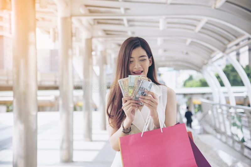 Women crazy shopaholic holding shopping bags , money ,credit card person at shopping malls.Fashionable Woman love online website stock photos