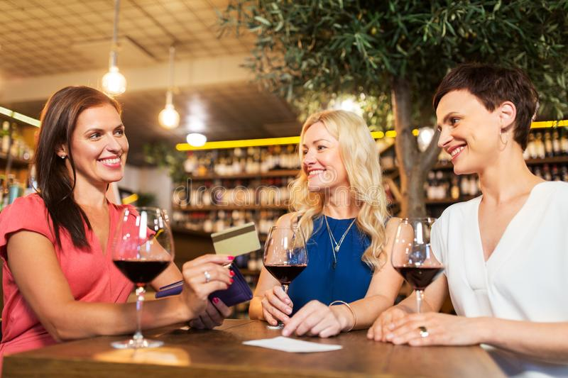 Women with credit card at wine bar or restaurant. Leisure, cashless payment and lifestyle concept - happy women with credit card paying bill at restaurant or stock images
