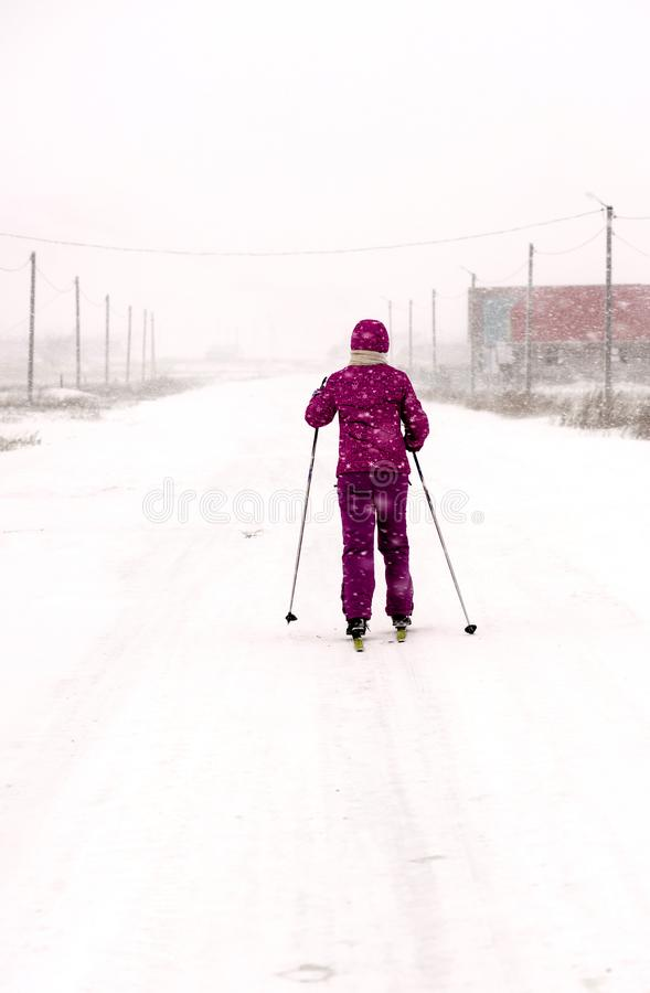 Women Cross Country Skiing on Road in Snow Storm royalty free stock photo