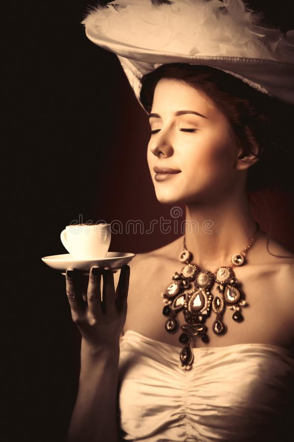 Women with cup on red background. Portrait of redhead edvardian woman with cup on red background stock photos