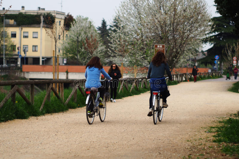Women cycling along Lainate canal. royalty free stock image