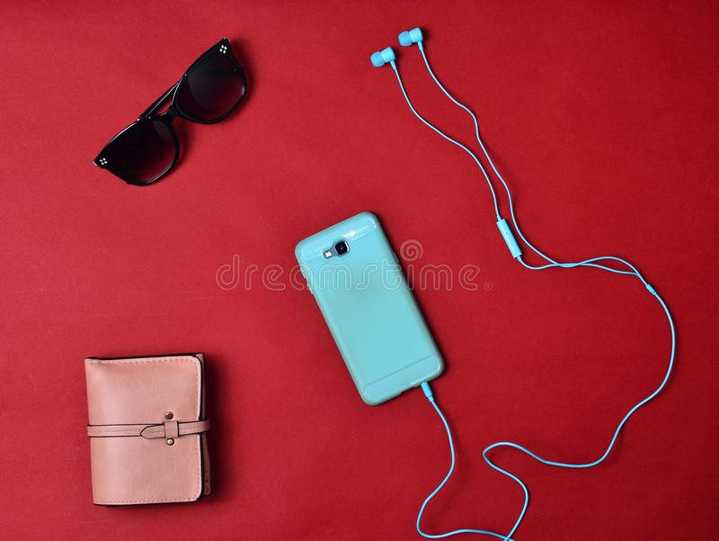 Women& x27 ; des accessoires de s sont rayés sur un fond rouge Smartphone, écouteurs, portefeuille, lunettes de soleil Configurat images stock