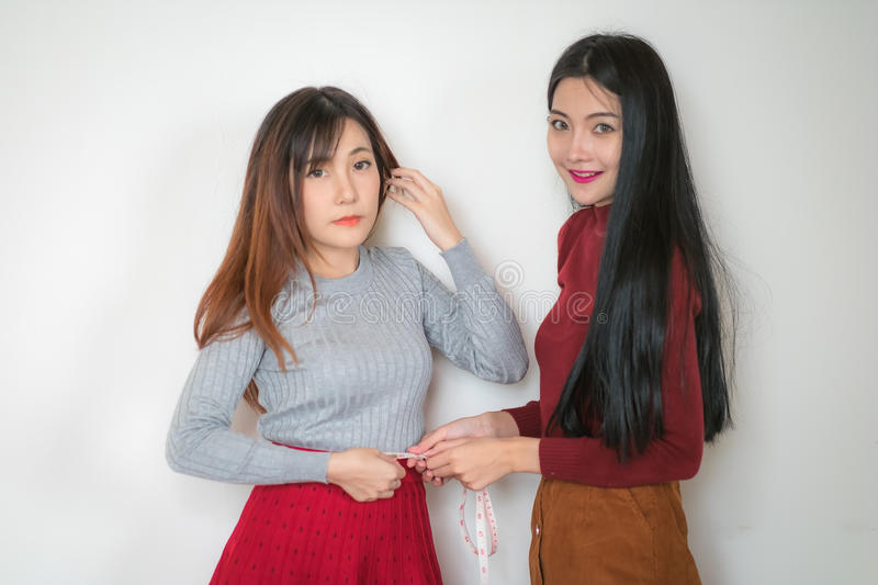 Women are on a diet is to measure the levels of the waist to ea. Two women are on a diet is to measure the levels of the waist to each other with tape centimeter royalty free stock photos