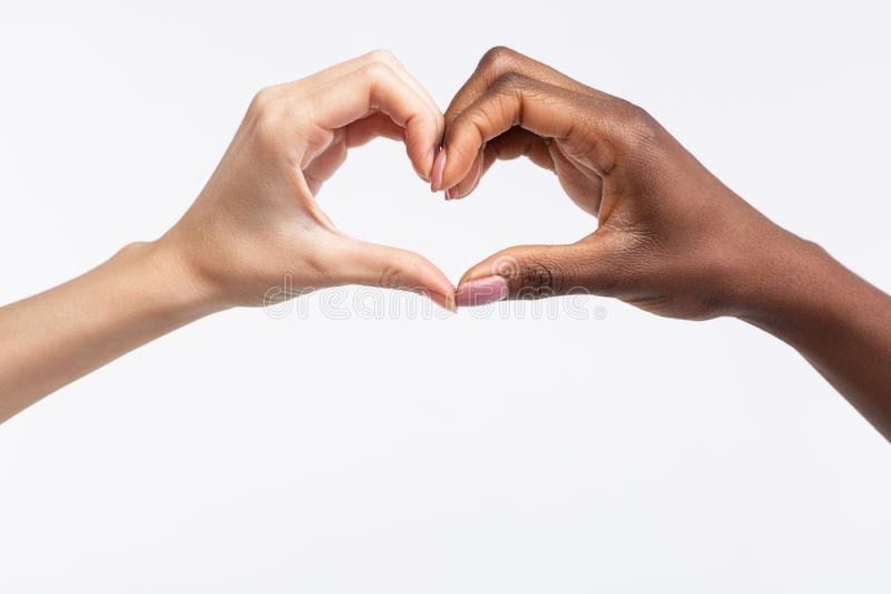 Women with different skin color making heart out of hands. Making heart. Close up of diverse women with different skin color making heart out of hands royalty free stock photography