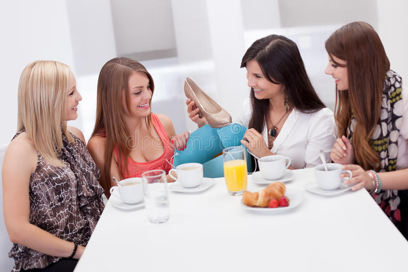 Women discussing footwear together stock images
