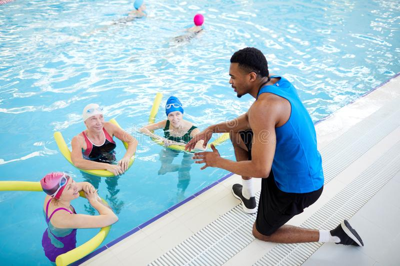 Women Doing Aqua Aerobics. High angle portrait of three mature women doing aqua aerobics in swimming pool with African-American fitness instructor, copy space royalty free stock photography