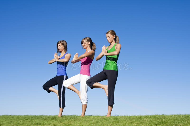 Women doing morning Yoga and Exercise. A group of three attractive women exercising and doing early morning yoga together stock photo