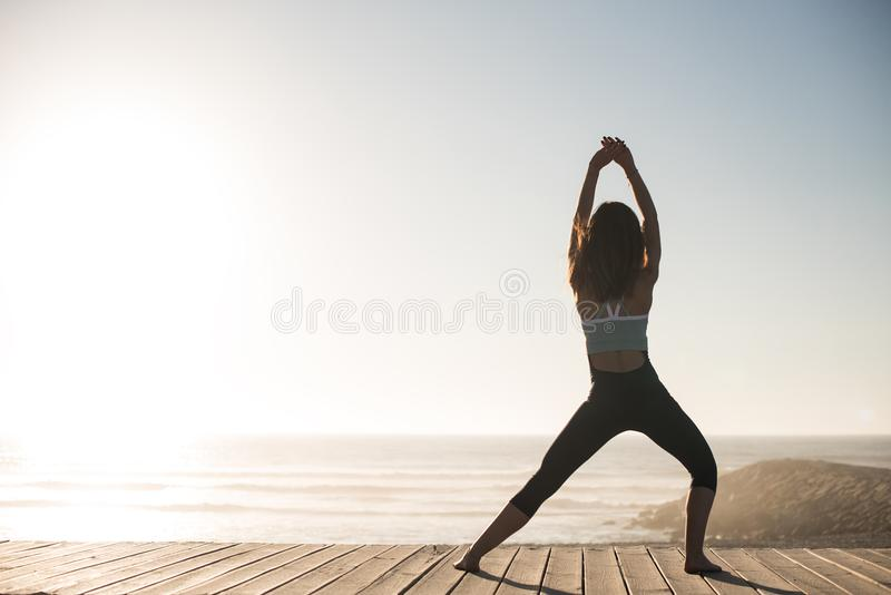 Women doing pilates on the beach. Women having a time doing pilates on the beach stock photo