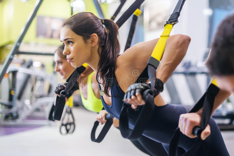 Women doing push ups training arms with trx. Fitness straps in the gym Concept workout healthy lifestyle sport royalty free stock images
