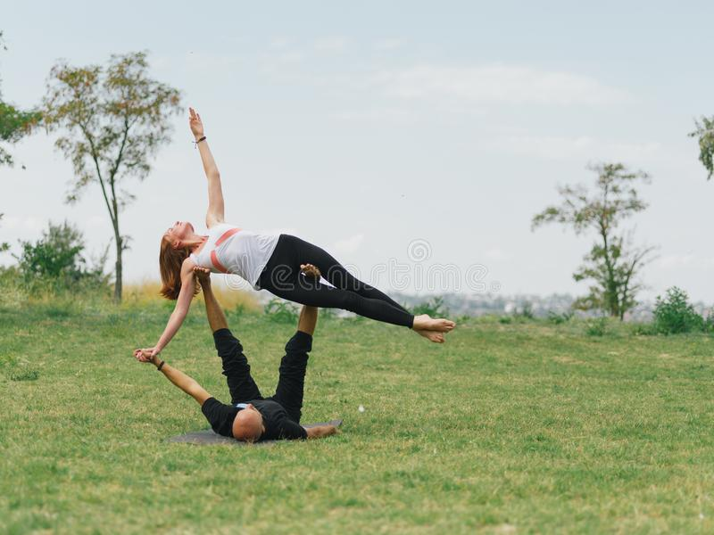 Healthy lifestyle modern activity. Young couple doing acro bird yoga pose. royalty free stock images