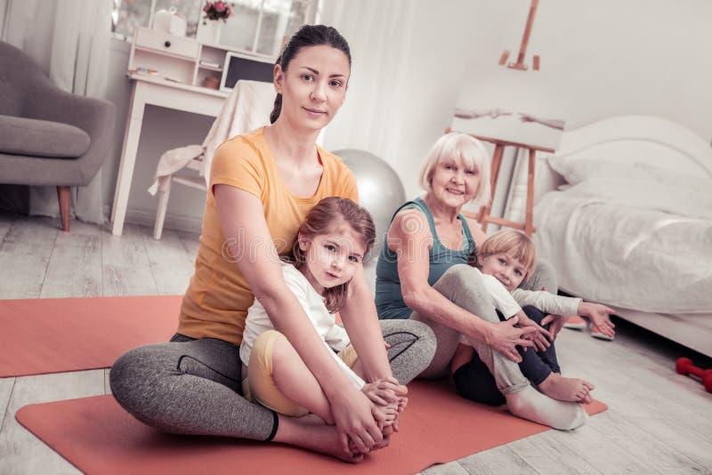 Women doing yoga training for children at home. Practising yoga at home. Women doing yoga training for children at home stock photos