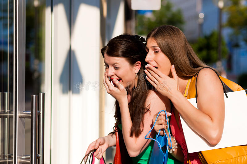 Women downtown shopping with bags. Two women being friends shopping downtown with colorful shopping bags, they are lolling into a glass store door and are amazed stock photos
