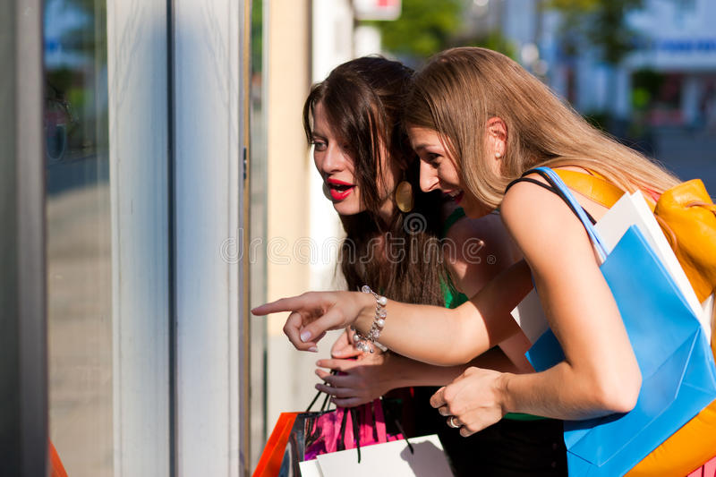 Women downtown shopping with bags. Two women being friends shopping downtown with colorful shopping bags, they are lolling into a glass store door and are amazed stock photo