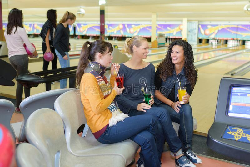 Women drinking in bowling alley royalty free stock images