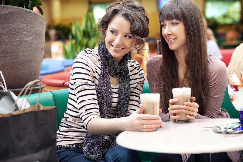 Women drinking coffee and chatting. Two beautiful women drinking coffee and chatting royalty free stock photography