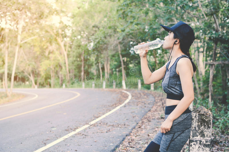 Women drinking water after running in road and forest background stock photos