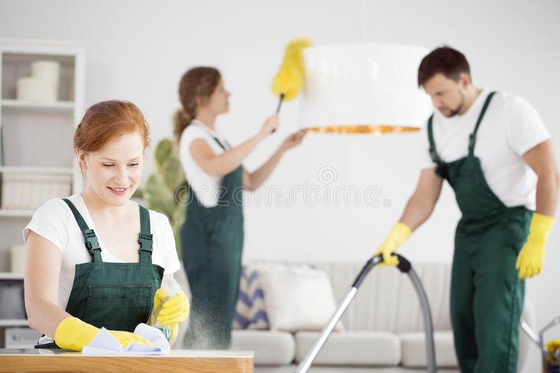 Women dusting and man vacuuming. Women dusting a table and lamp and a men vacuuming in green overalls and yellow gloves royalty free stock images