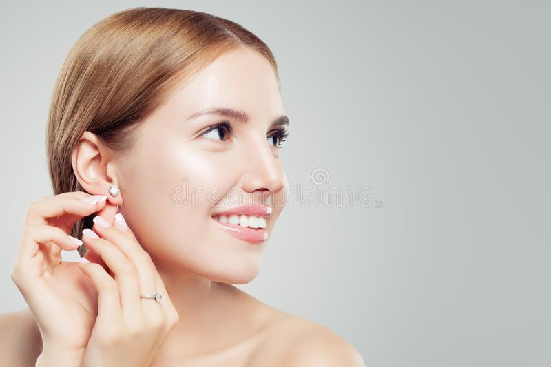 Women earring jewelry model. Cheerful woman with diamond earrings and ring, beautiful face closeup royalty free stock photos