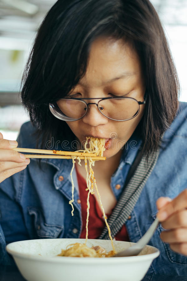 Women eating egg noodle with crispy pork from chopsticks and met stock image