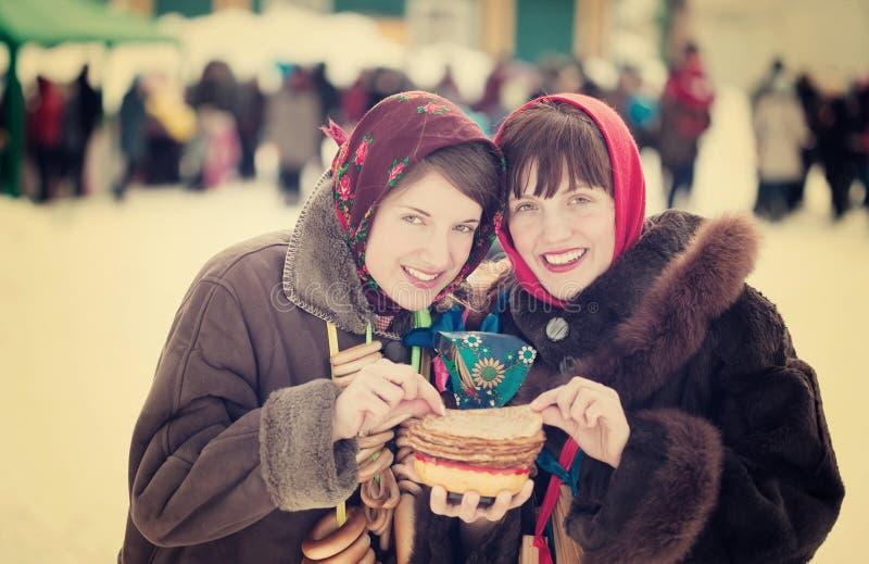 Women eating pancake during Pancake Week. Women in traditional clothes eating pancake during Pancake Week royalty free stock image