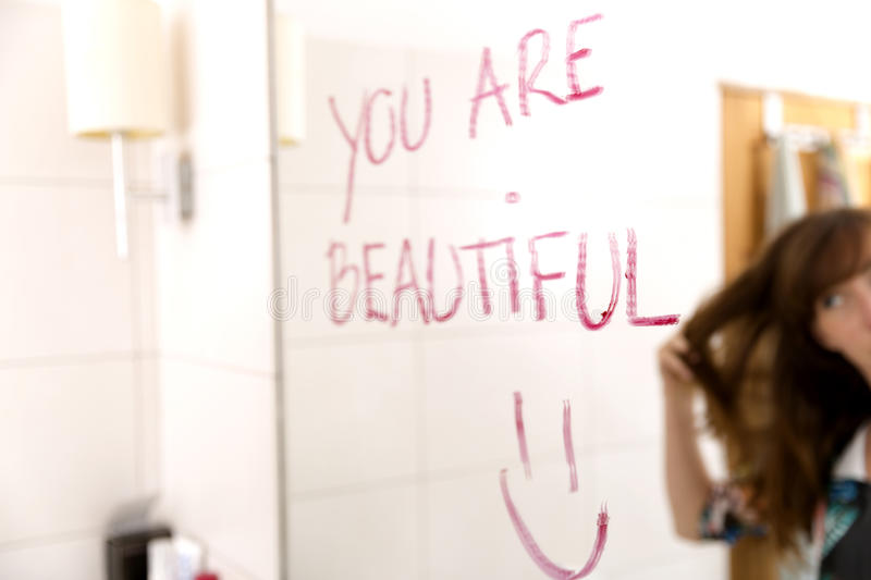 Women encouraging herself by writing words you are beautiful on mirror with lipstick.  stock photo
