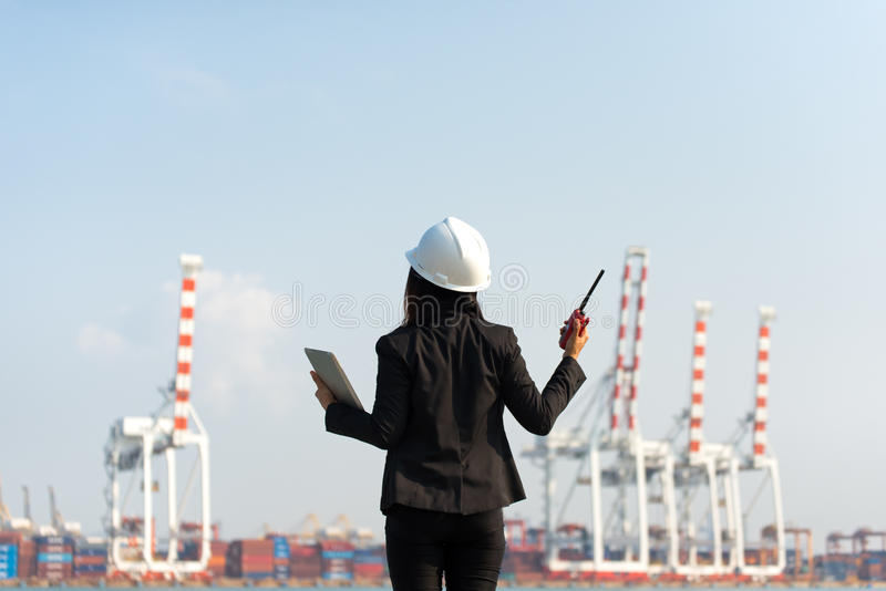 The women engineer holding radio and working with container Cargo freight ship in shipyard at dusk for Logistic Import Export back stock photos