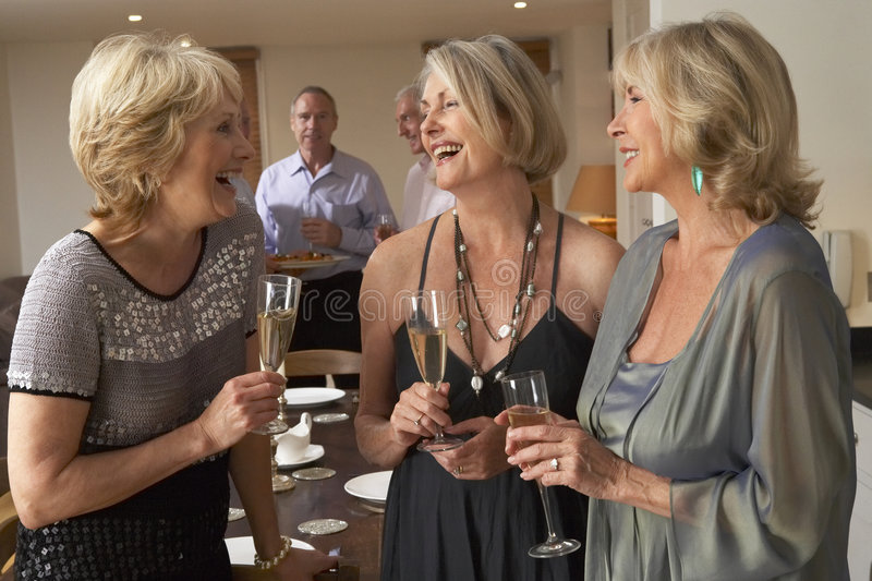 Women Enjoying Champagne At A Dinner Party. Women Chatting And Enjoying Champagne At A Dinner Party royalty free stock photos