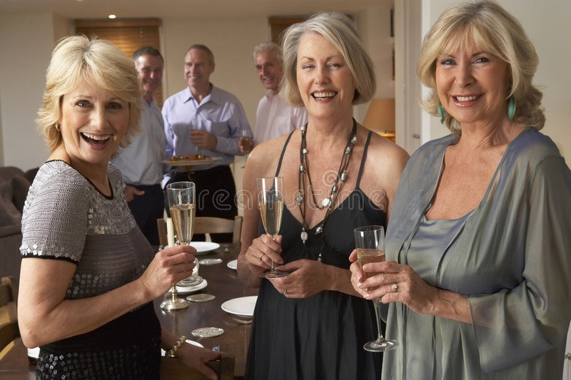 Women Enjoying Champagne At A Dinner Party. Women Chatting And Enjoying Champagne At A Dinner Party royalty free stock images