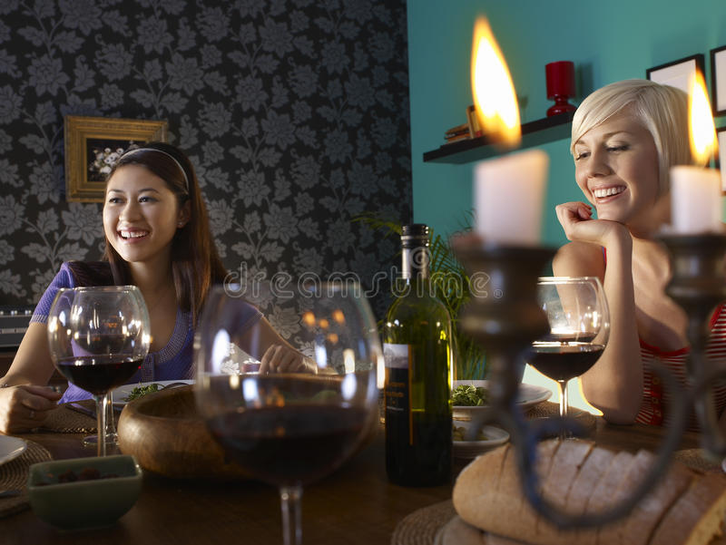 Women Enjoying Dinner Party. Smiling young multiethnic women enjoying dinner party royalty free stock photography