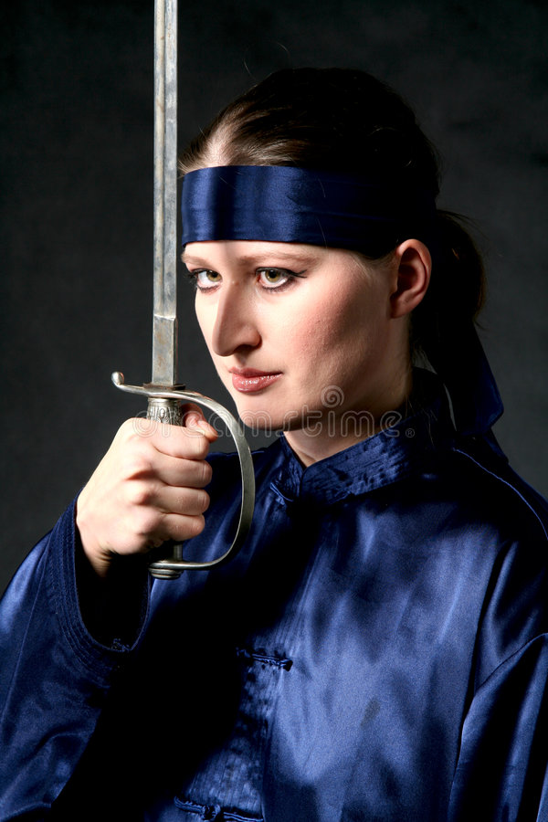Women With Epee. Women in chinese costume with epee close to face. Make-up stock images