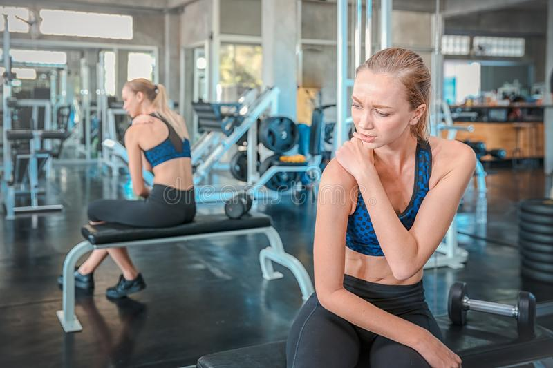 Women exercise already painful. Young caucasian female having pain in her arm while workout at the gym. Woman feeling strong pain stock images