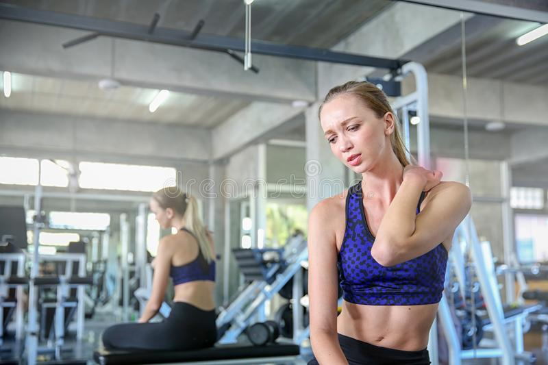 Women exercise already painful. Young caucasian female having pain in her neck while workout at the gym. Woman feeling strong pain. In muscles after exercising royalty free stock photography