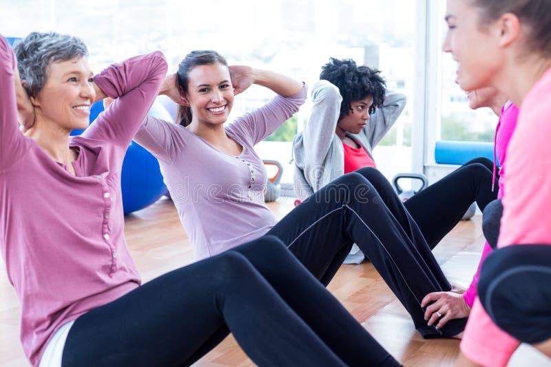 Women exercising on floor with hands behind head. In fitness studio stock images