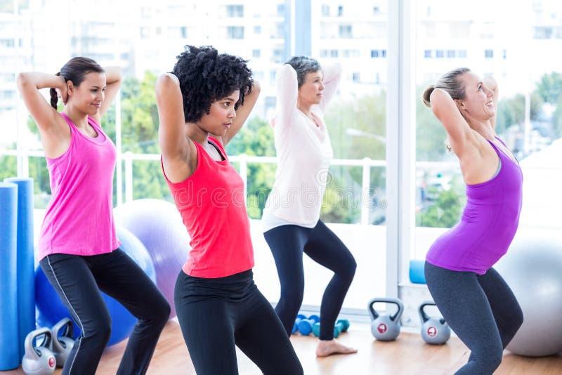 Women exercising with hands behind head. In fitness studio stock photos