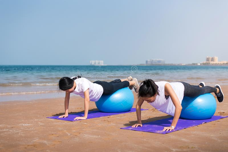 Women exercising with pilates ball on the beach. Women exercising with pilates yoga ball on the beach exercise fitness workout women summer friends girls royalty free stock image