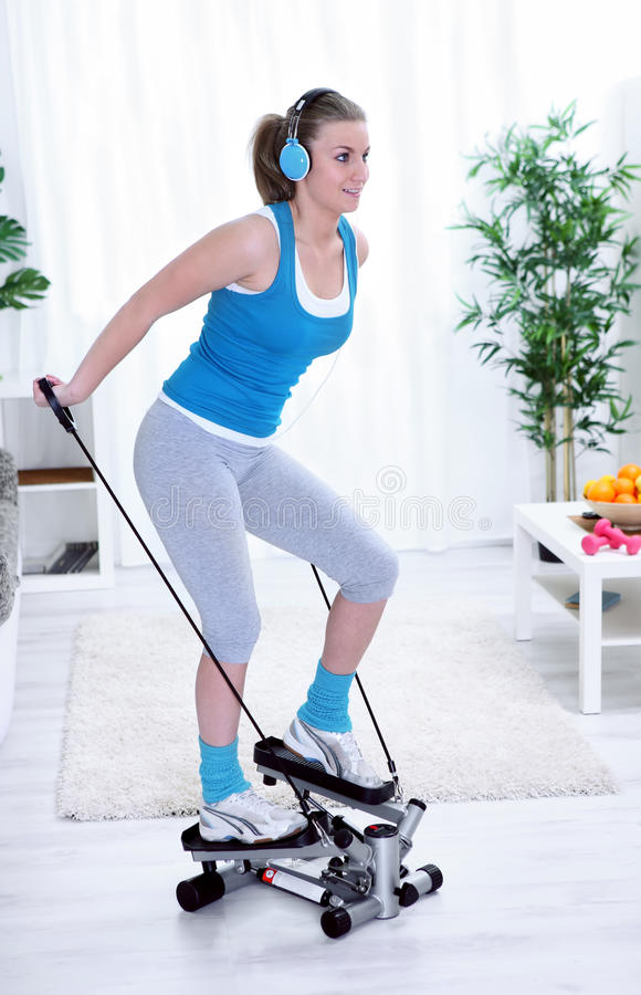 Women exercising on stepper. Happy young pretty woman exercising on stepper at home stock photo