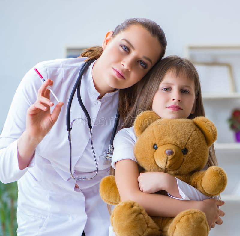 Woman female doctor examining little cute girl with toy bear. The women female doctor examining little cute girl with toy bear stock images