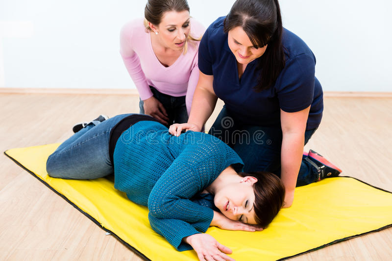 Women in first aid class training to position injured person royalty free stock photography