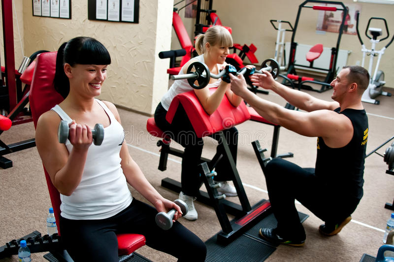 Women in fitness club. Two women working out in a fitness club, assisted by professional instructor stock photo