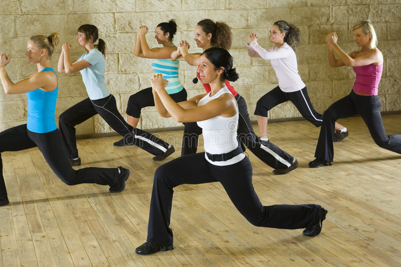 Women at fitness club. A group of women exercising with fitness instructor in the gym. Focus on the woman in white shirt. Side view royalty free stock images
