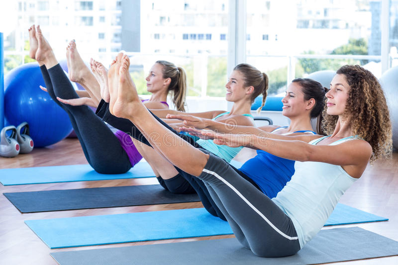 Women in fitness studio doing boat pose. Fit women in fitness studio doing boat pose on exercise mat royalty free stock photography