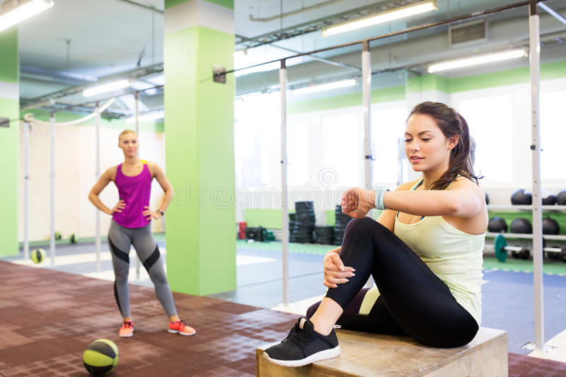 Women with fitness tracker and ball in gym. Sport, training and people concept - women with fitness tracker and medicine ball in gym stock photo