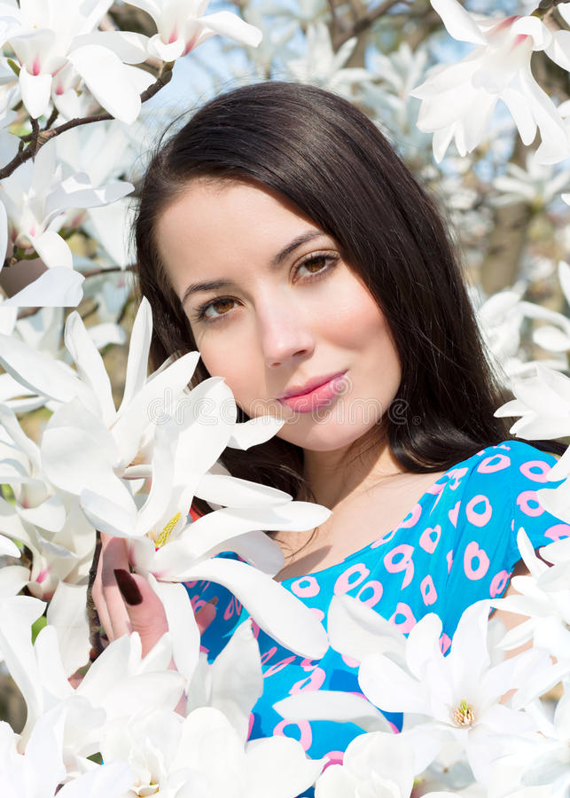 Women and flowers of Magnolia. Young woman surrounded by flowers of Magnolia royalty free stock photos
