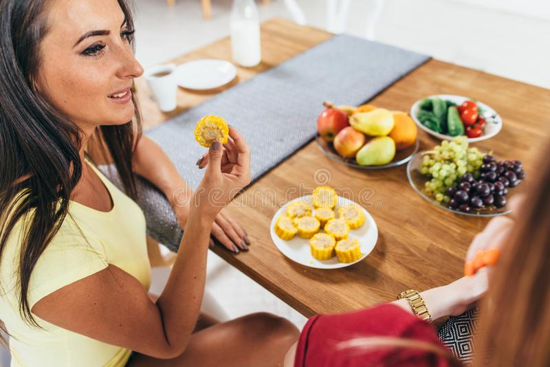 Women friends eating fruits and vegetables in kitchen. Healthy nutrition. Low calorie meal. Women friends eating fruits and vegetables in kitchen. Healthy royalty free stock photography