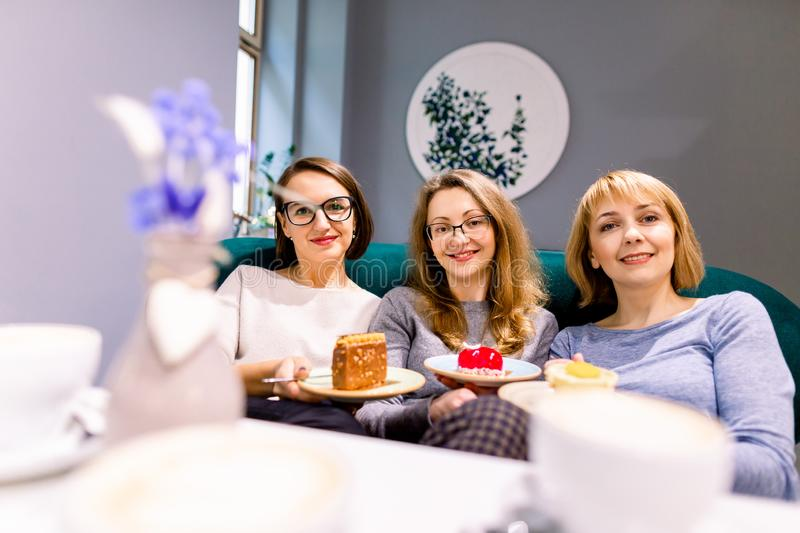 Women friends looking at camera, smilikng, holding cakes, three girl friends drinking coffee in the cafe and eating. Desserts, women during lunch time in cafe royalty free stock images