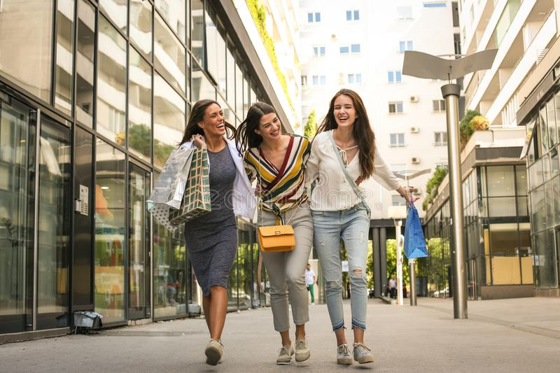 Women friends walking trough city, happy. royalty free stock images