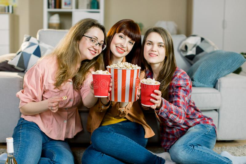 Women friendship, home party. Three beautiful funny young girl friends with popcorn in hands sitting on the floor in stock photography