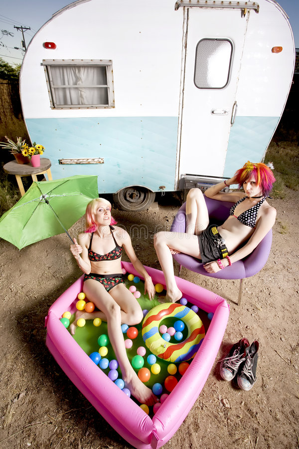 Women in front of a trailer. Woman relaxing with in an inflatable play pool royalty free stock photography