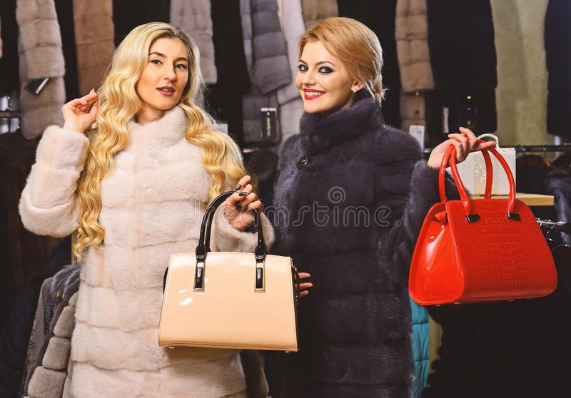 Women in fur coats with bags in fur shop. Winter clothing and glamour concept. Ladies with makeup shopping in fashion royalty free stock photos