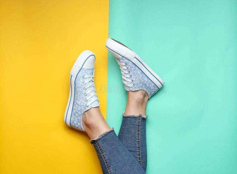 Women& x27; gambe di s in jeans stretti e lacerati, scarpe da tennis su fondo pastello blu giallo Vista superiore, minimalismo, s immagini stock libere da diritti